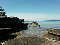 Large boulders protruding from the clear waters around the Georgian Bay shoreline of Manitoulin Island.