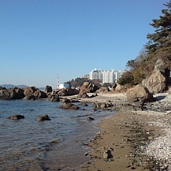 View of a beach covered in pebbles, rocks and boulders. Skyscrapers peek out and up from around the bend.