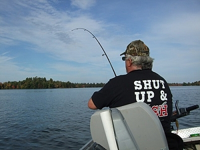 Fisherman reeling in a cast, wearing a funny yet appropriate t-shirt.