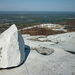 A pointy white quartzite boulder stands over a magnicifent view from Silver Peak.
