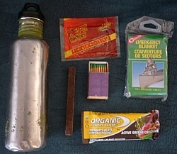 Emergency winter gear (clockwise from left): water bottle, hand warmer, emergency blanket, protein bar, fire starter, waterproof matches.