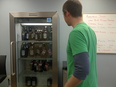 A Stack Brewing employee stands before a stocked beer fridge.
