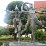 A statue of two women and a man dancing artistically in the nude, seen near the fish market in the Dadaepo neighbourhood of Busan, South Korea.