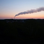 View of Sudbury's smokestack set against a colourful sunset sky.