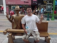 Travel with a buddy! Here, a statue sits on a pedestrian bench in Busan, South Korea, and a CouchSurfer sits next to it in the same pose.