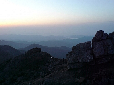 View from a mountain peak at sunrise, light mist hovering above the mountains, the sun piercing the cool blue morning sky in the distance.