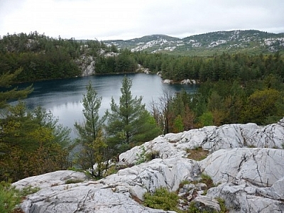 Landscape of lakes and white quartzite mountains seen while hiking the La Cloche Silhouette Trail