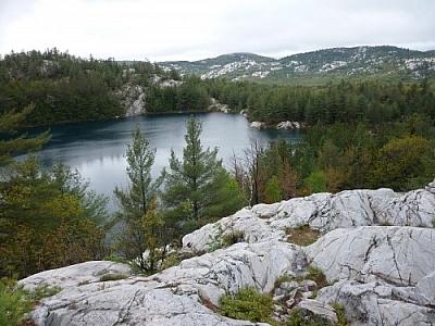 Landscape of lakes and white quartzite mountains seen while hiking the La Cloche Silhouette Trail