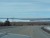 View of a frozen Lake Superior, Highway 17 skirting along its shore, and the tip of a vehicle's hood just visible in the foreground.