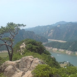 View of a river-like lake snaking through the mountains in Woraksan National Park, an oddly shaped tree growing from a hillside.