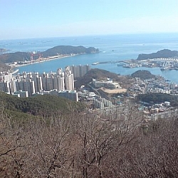 Panoramic view of the Port of Dadaepo, Dusong Peninsula in the distance and ships floating on the ocean beyond.