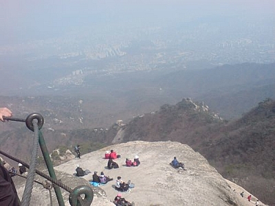 People resting on a steep mountain ledge at Bukhansan National Park.