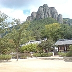 A temple before a shapely peak rising in the background at Juwangsan National Park.