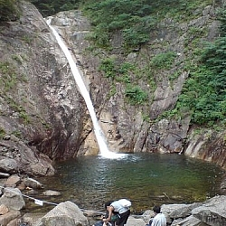 A waterfall pouring into a rocky pool, a few Korean boys admiring the view.