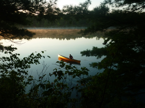 A canoeist heading out for a morning paddle on Big Clear Lake.