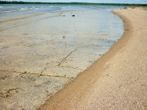 The ebb and flow of waves reveals alvar pavement beneath the sand at Misery Bay.