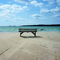 A bench on a sandy beach overlooks Misery Bay.