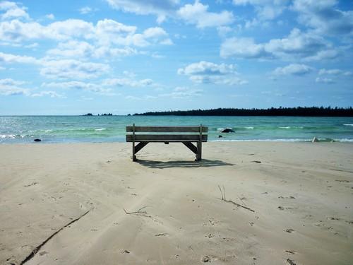 A bench on a sandy beach overlooks Misery Bay.