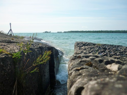 Waves crash through a crevice in coastal rocks covered with pit karren.
